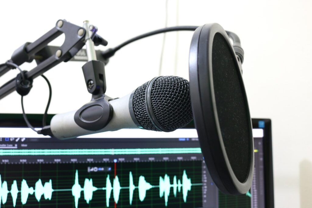 Microphone in front of a waveform in an audio editor on a computer