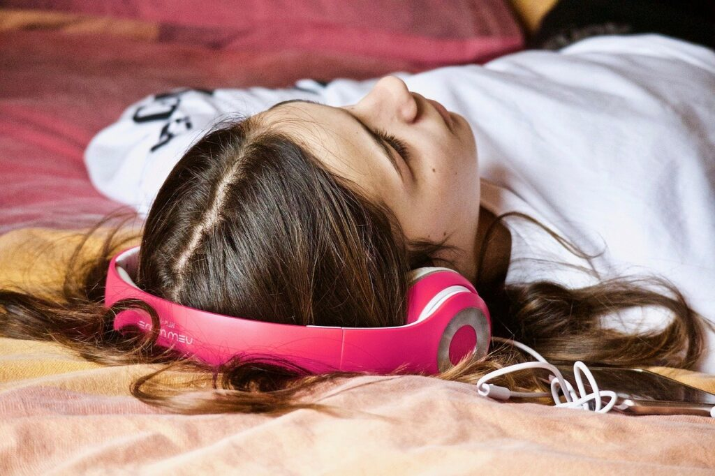 Girl listening on her bed, with headphones on